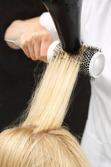 Modelowanie włosów na szczotkę. Kobieta u fryzjera, fryzjer modeluje włosy na okrągłej szczotce