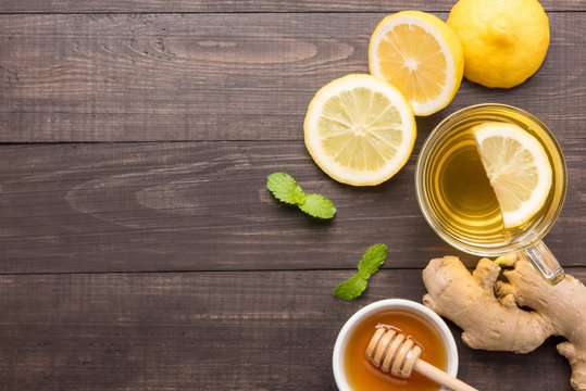 Cup of ginger tea with lemon and honey on wooden background