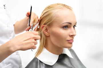 Kobieta u fryzjera.Strzyżenie włosów w salonie fryzjerskim