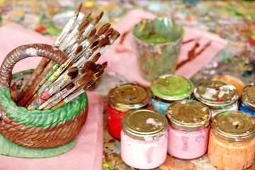 Many Paintbrushes And Paint In The Jar On The Palette