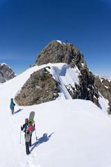 Snowboarders walking uphill for freeride