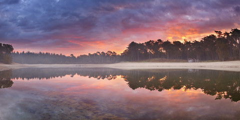 Reflections of sunrise at a quiet lake in The Netherlands