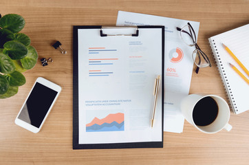Business analytics and strategy. Top view of business workspace with stationary, smartphone and coffee cup. Concept for website banner and marketing material, for business, marketing, finance.