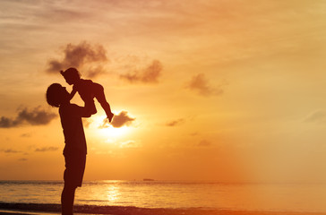 Father and little daughter play silhouettes at sunset