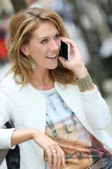 Trendy girl talking on phone in the street