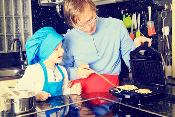 father and son preparing waffles in kitchen