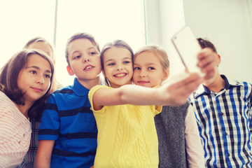 group of school kids taking selfie with smartphone