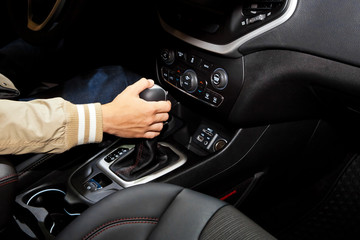 Hand holding automatic transmission in car