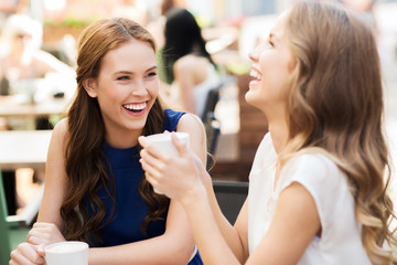 smiling young women with coffee cups at cafe