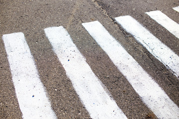 incorrect road markings. too narrow strip of road marking on a pedestrian crossing zebra