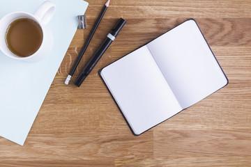 Mesa de trabajo con libreta en blanco y objetos azules, blancos y negros
