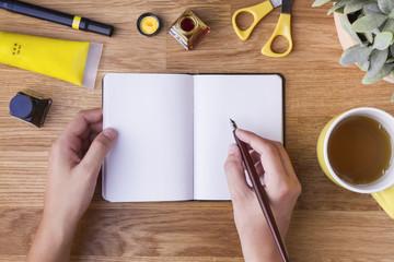 Mano con pluma escribiendo en libreta en blanco y objetos amarillos
