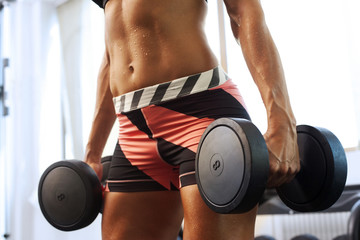 Young beautiful woman with muscles lifting weights showing abdom
