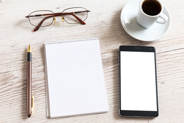 Notebook with glasses, pencil, smart phone and coffee cup on wooden table