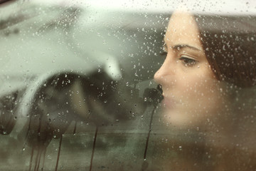 Sad woman looking through a car window