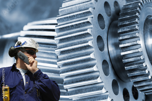 Wall mural mechanic, worker with large cogwheel and gears machinery