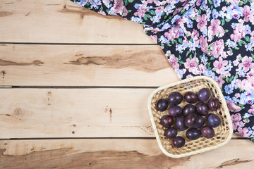 Ripe plums on the wooden background