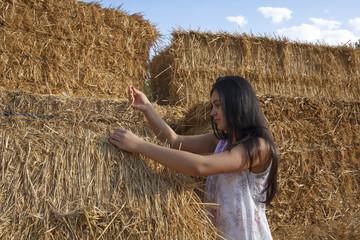Adolescente en las alpacas de heno al final de verano. Chica joven disfrutando en el campo de una tarde de verano.