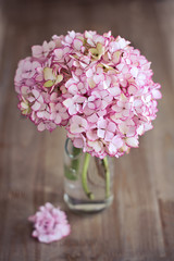 Pink hydrangea flowers in a glass vase on a wooden table.