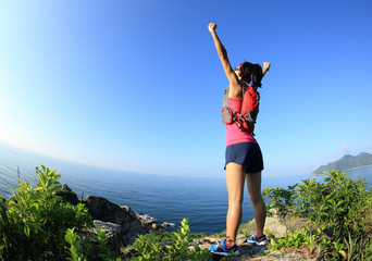 cheering young fitness woman open arms on seaside mountain peak