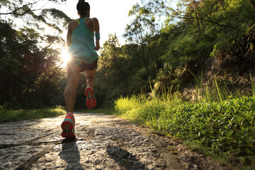 Runner athlete running on forest trail. woman fitness jogging workout wellness concept. Wall mural