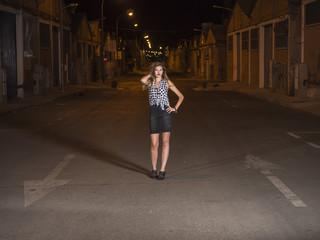 mujer modelo profesional posando en carretera por la noche