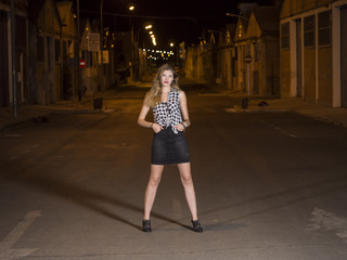 mujer modelo profesional posando de noche en la calle con las manos en los bolsillos
