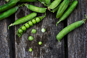 Young fresh green peas on wooden background