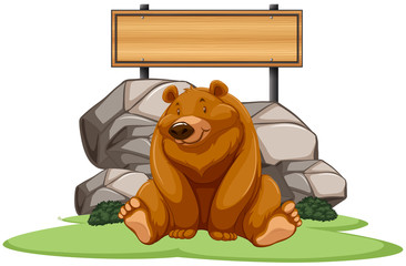 Grizzly bear sitting next to the sign