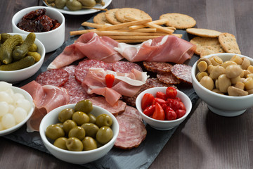 deli meat snacks, sausages and pickles on a blackboard