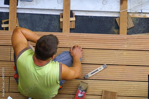 ein handwerker verlegt terrassendielen stockfotos und lizenzfreie bilder auf. Black Bedroom Furniture Sets. Home Design Ideas