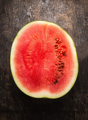 half of watermelon on rustic wooden background, top view