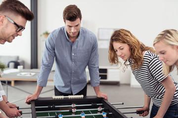 kollegen spielen kicker im büro
