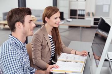 junges team schaut gemeinsam auf computer