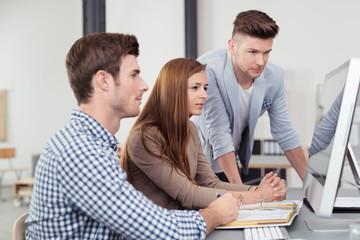 team im büro schaut konzentriert auf computer