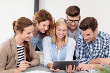 junges team im büro, schaut auf tablet