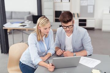 zwei leute sitzen am schreibtisch und schauen auf laptop