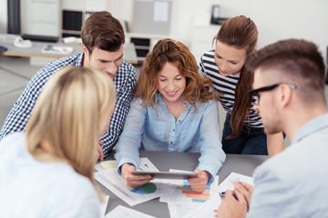 junges team im büro schaut auf tablet-pc