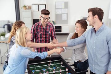 kollegen geben sich die hand nach dem kickerspiel