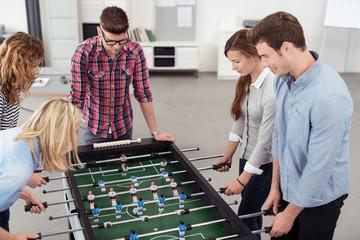 kollegen spielen kicker am arbeitsplatz