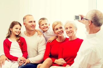 smiling family with camera at home