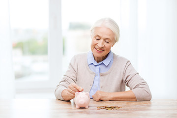 senior woman putting money to piggy bank at home