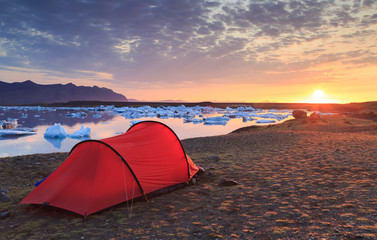 Fotomurales - Red tent during a beautiful sunrise at the Jokulsarlon lake on Iceland.