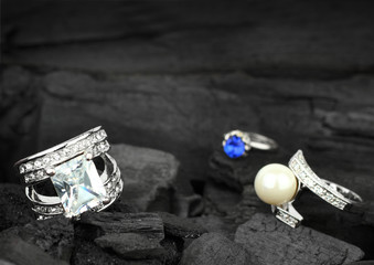 Few jewelry rings with brilliants, gems and pearl on dark coal b