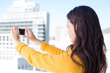 Pretty brunette taking photos with her smartphone