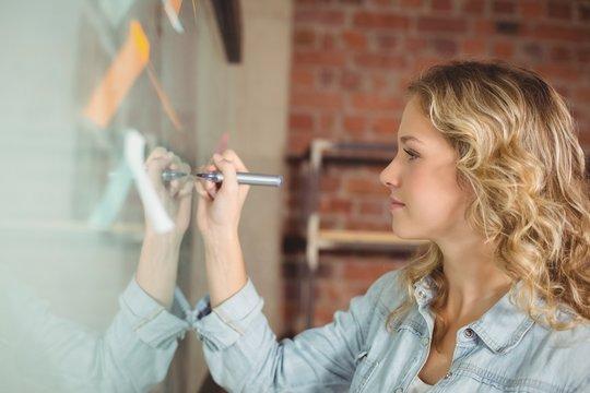 Creative beautiful businesswoman writing on board in office