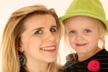 Blond woman holding a cute blond girl wearing a green hat