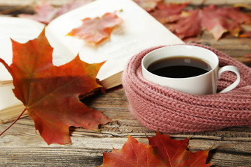 Cup of coffee with autumn leaves and a warm scarf on brown wooden background