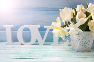 White daffodils and tulips  flowers in bucket and word love