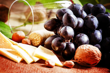 Cheese, blue grapes, vine, nuts and a glass, selective focus